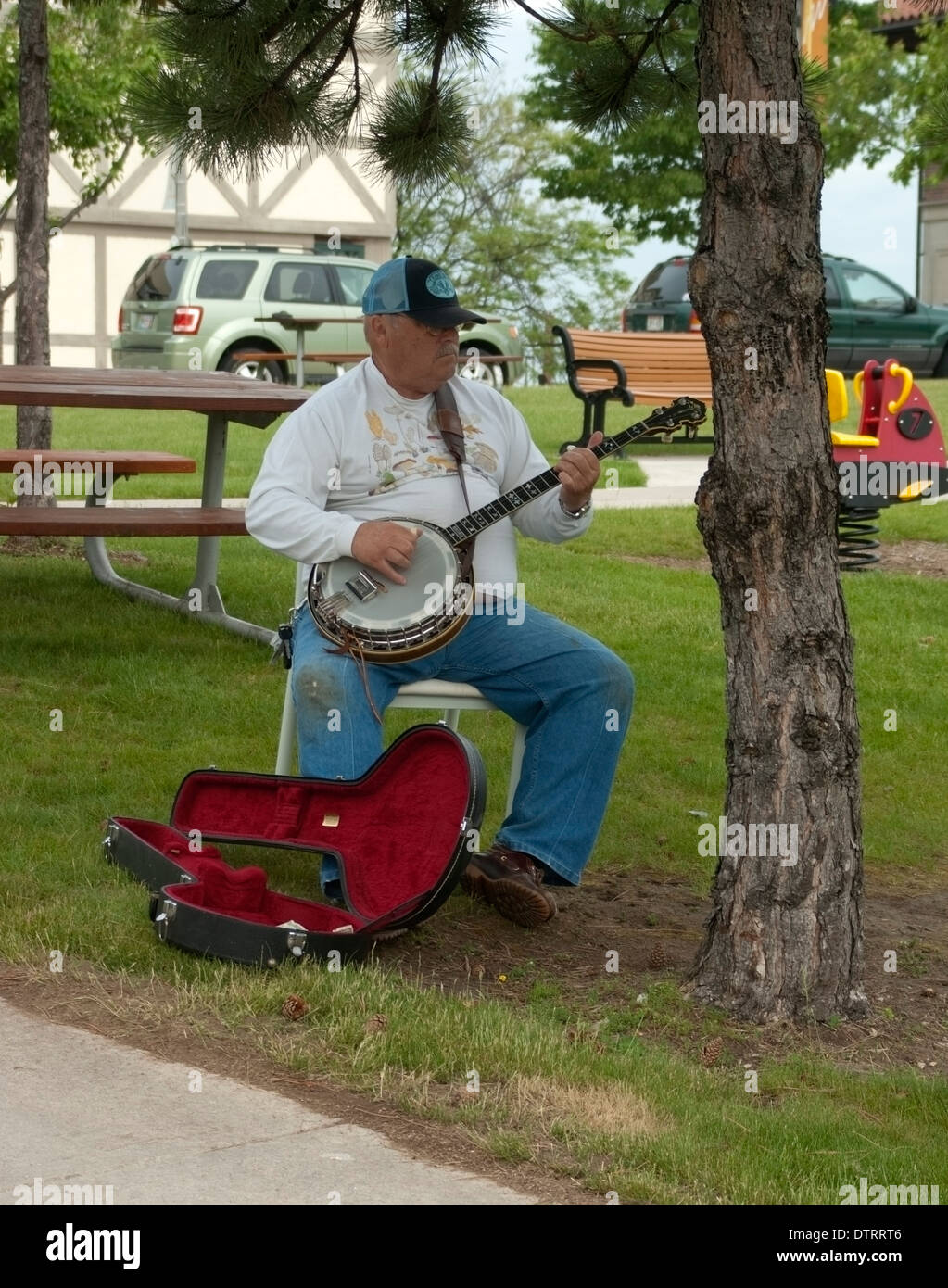 Banjo player in public park - Stock Image