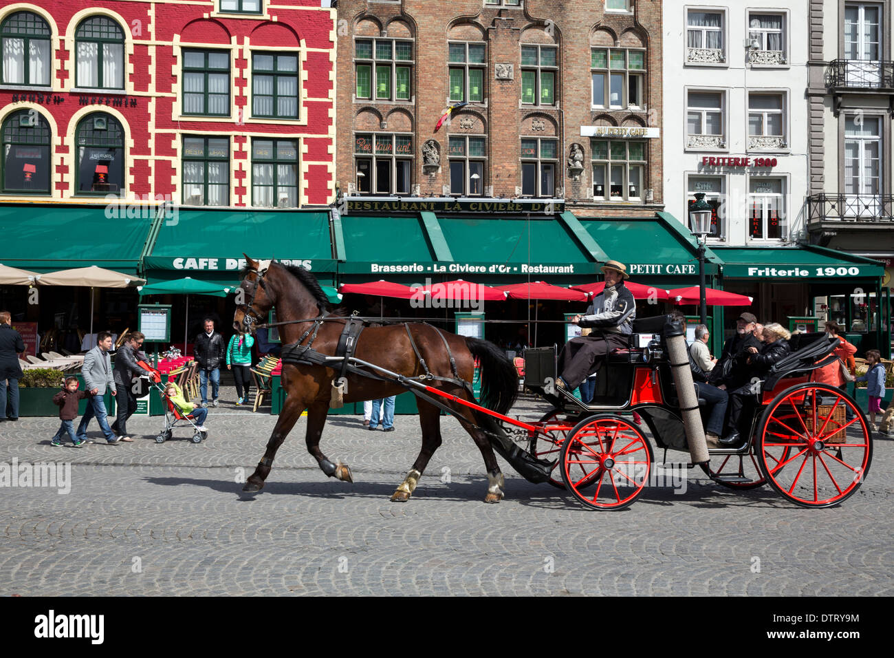 Horse drawn carriage transporting tourists through the Markt in Bruges - Stock Image