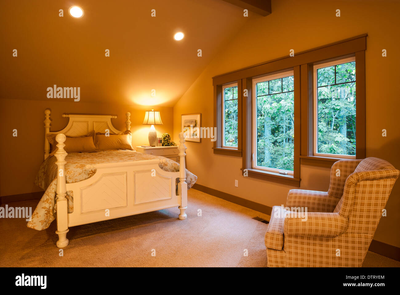 Small bedroom in luxury home with bed, chair, and nightstand, showing woods outside of window. - Stock Image