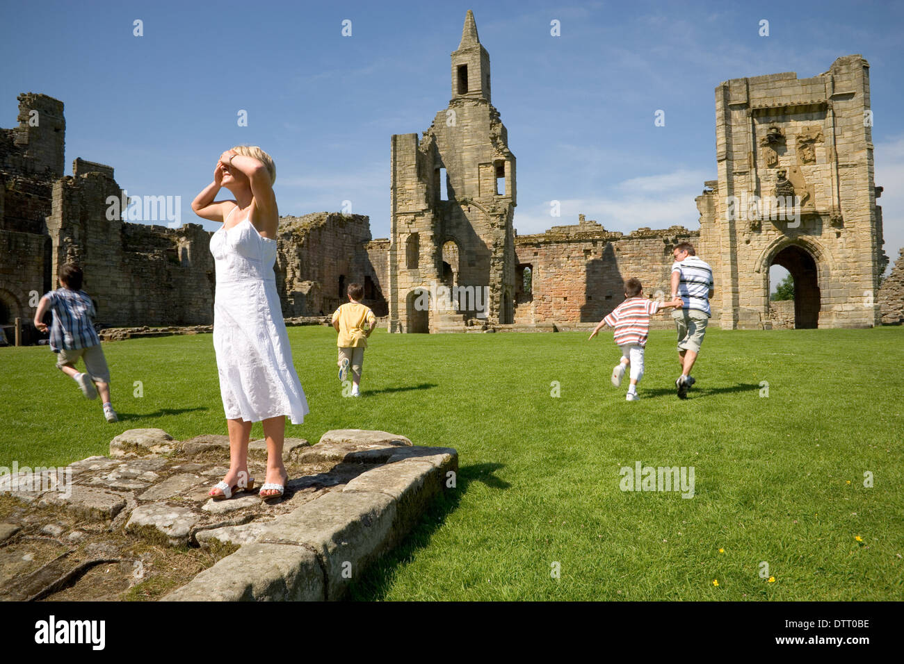 Family playing hide and seek at Warkworth Castle, Northumberland. - Stock Image