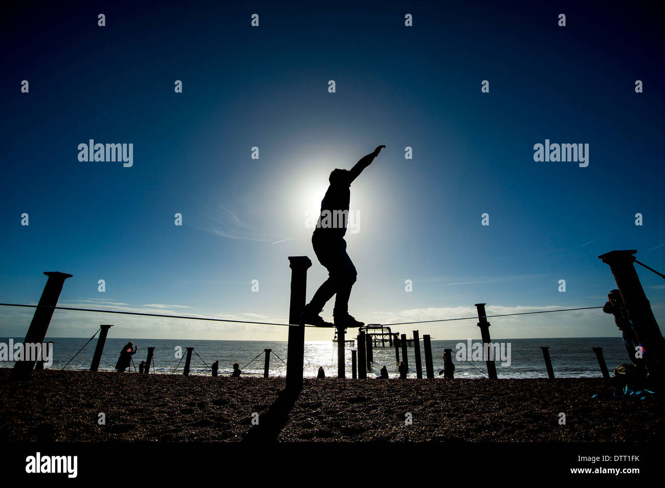 A tightrope walker practices in the sunshine in front of the west pier in Brighton, Sussex, UK Stock Photo