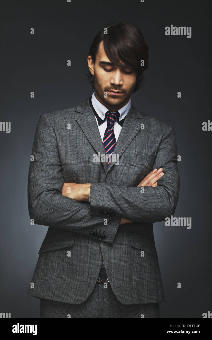 Young male business executive with his arms crossed looking down in thought. Thoughtful businessman in suit standing. - Stock Image