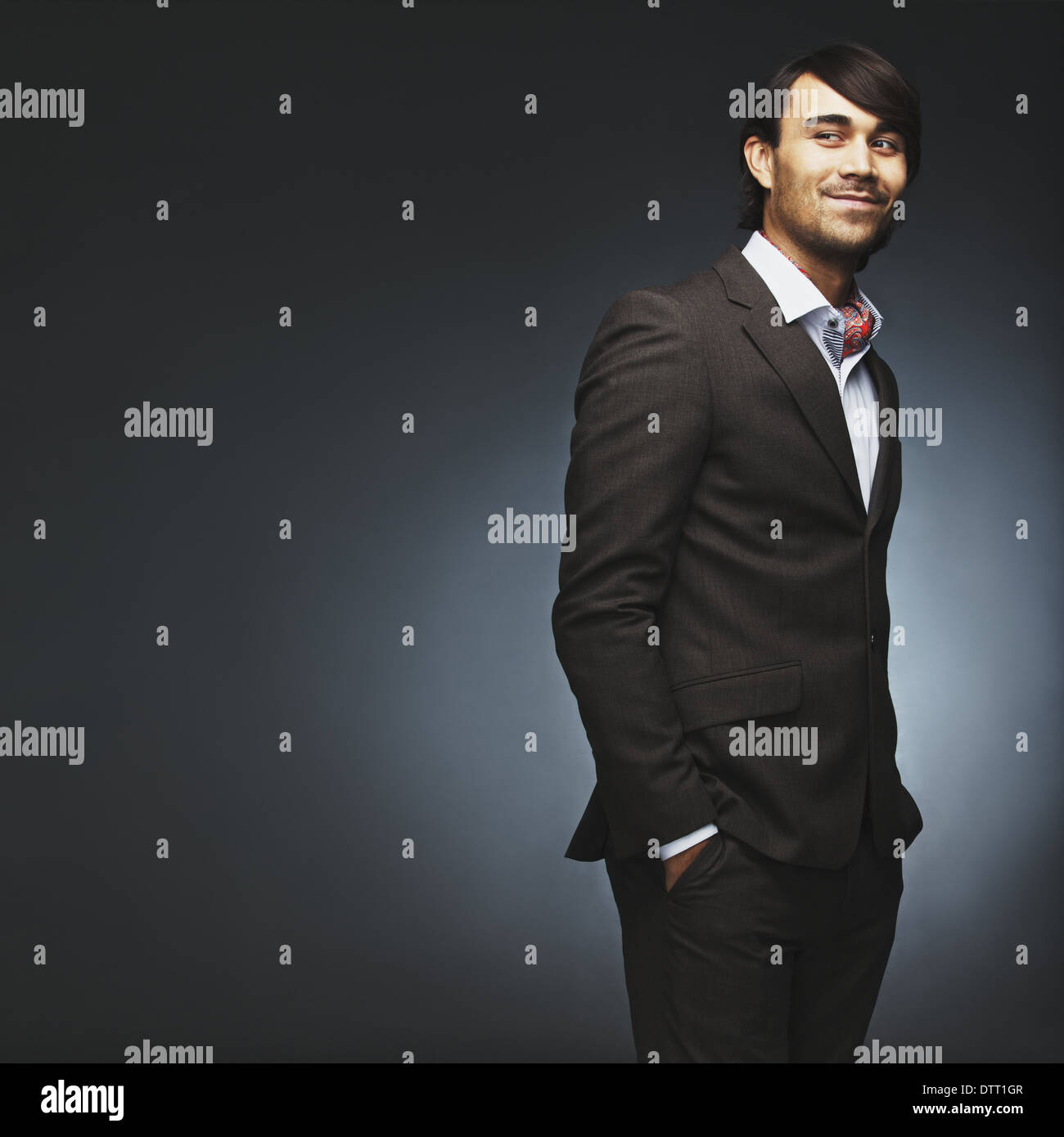 Attractive young man wearing suit standing with his hands in pocket looking over shoulder. Handsome male fashion model posing. - Stock Image