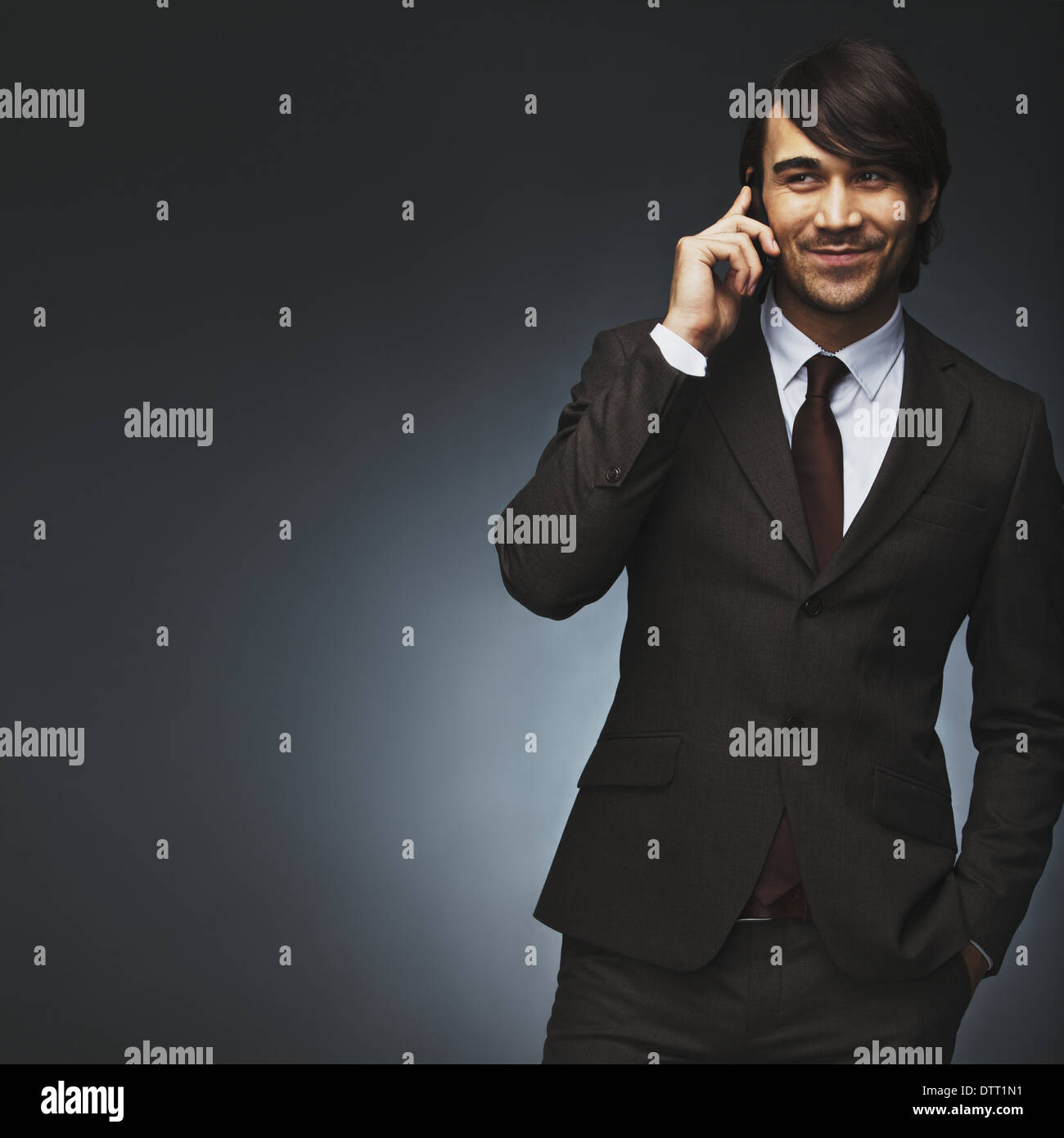 Asian man talking on mobile phone. Handsome young mixed race man on black background. Professional young businessman calling. - Stock Image