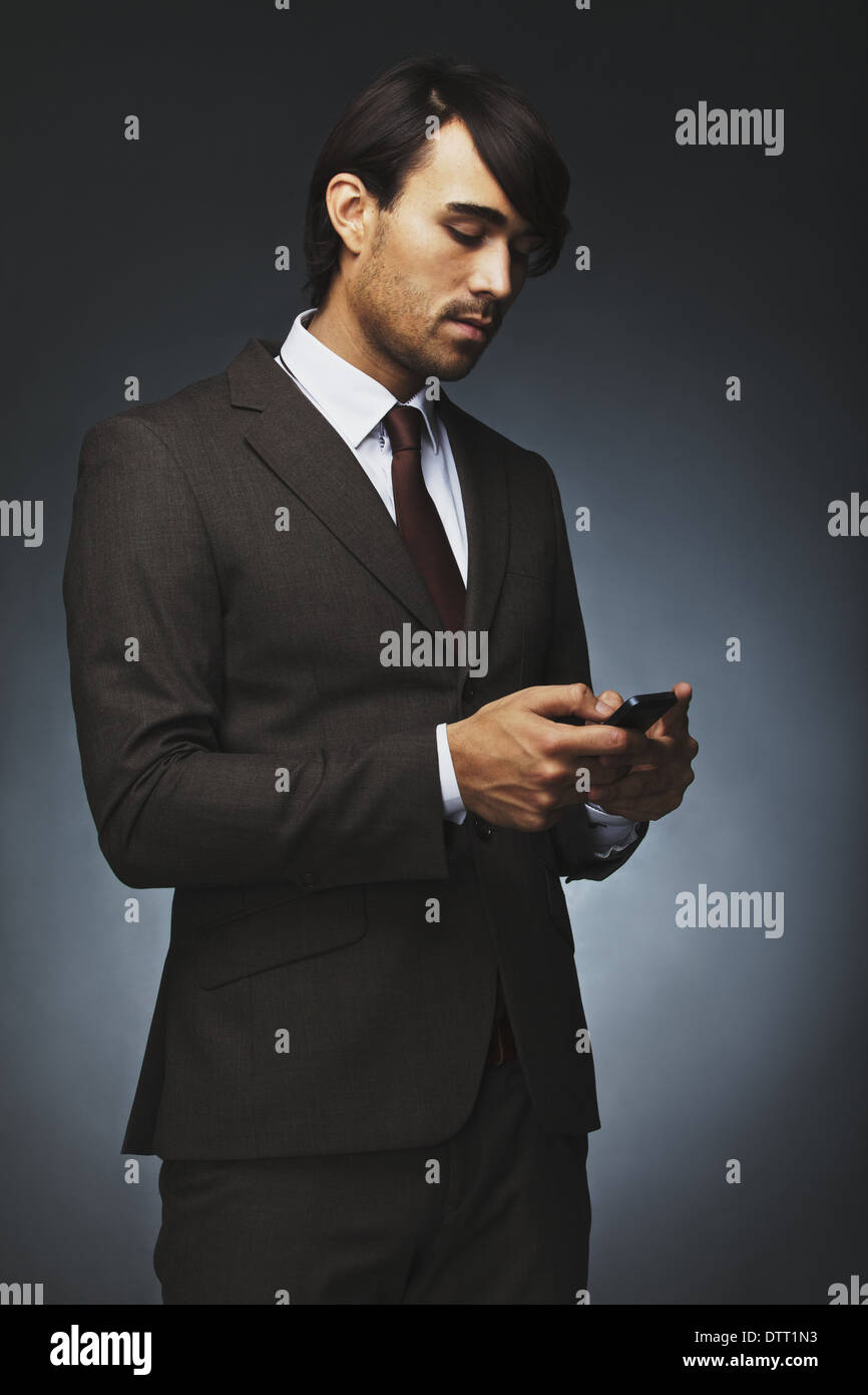 Handsome young business man texting on his phone. Male executive reading test message on his mobile phone. Male model in suit. - Stock Image
