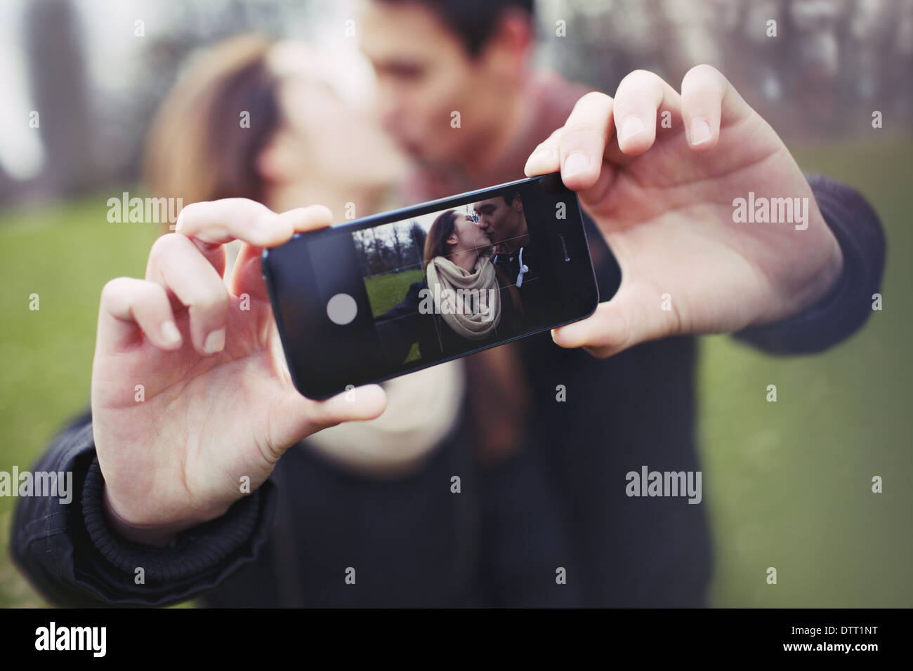 Loving young couple photographing themselves with a mobile phone while kissing at the park. Focus on smart phone. - Stock Image