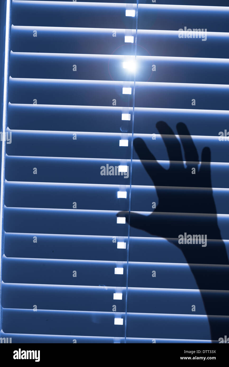 Conceptual image of being trapped and helpless. Shadow of a hand reaching for closed window blinds with sunlight - Stock Image