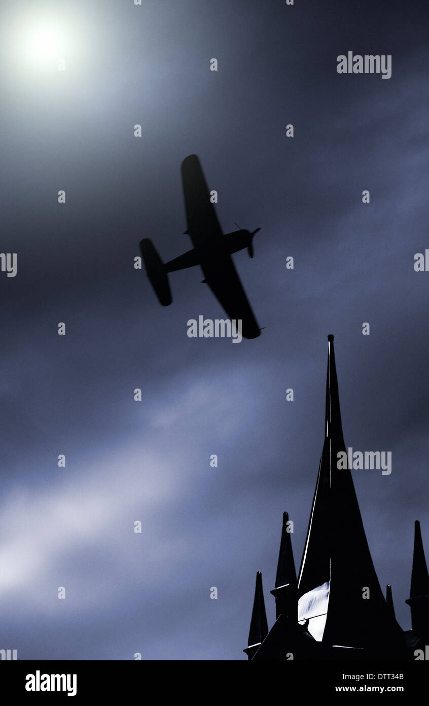 Old propeller fighter plane flying on a moonlit sky over building rooftop - Stock Image