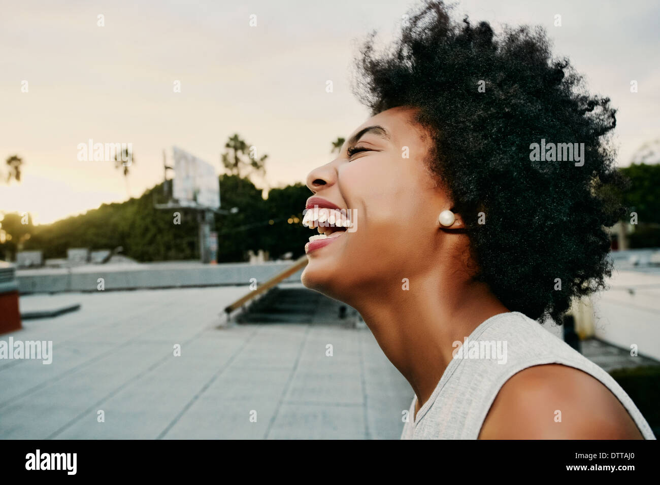 Mixed race woman laughing on urban rooftop Stock Photo