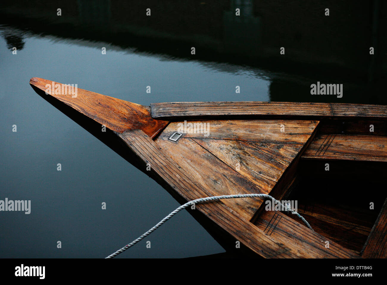 Wooden bow of Cambridge Punt with white rope trailing off it ,dark water - Stock Image