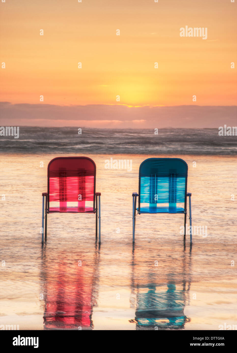Lawn chairs in waves on beach at sunset - Stock Image