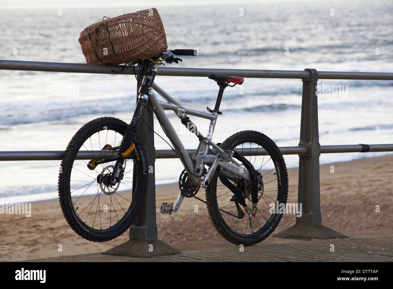 bike with basket on railing at Boscombe beach in February - Stock Image