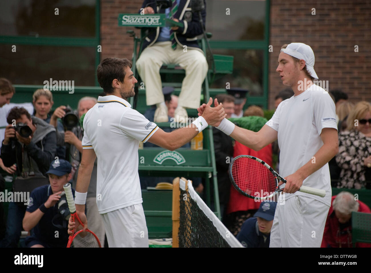 Two male tennis players shake hands after match at Wimbledon championship - Stock Image