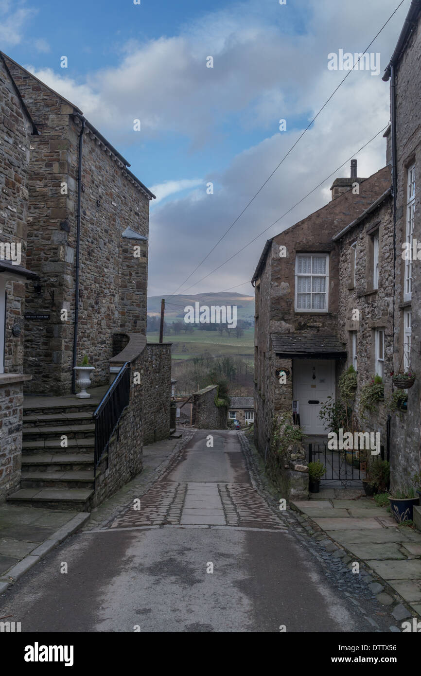 Stone built houses, on either side of a narrow road leading downhill Stock Photo
