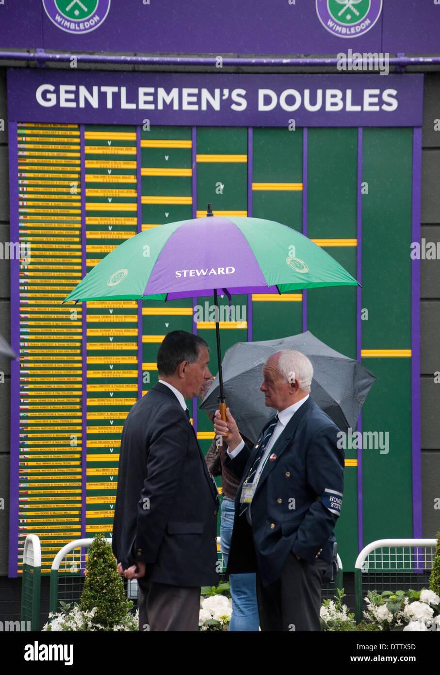 Wimbledon Tennis officials with open umbrella standing in front of Gentlemen's Doubles scoreboard - Stock Image