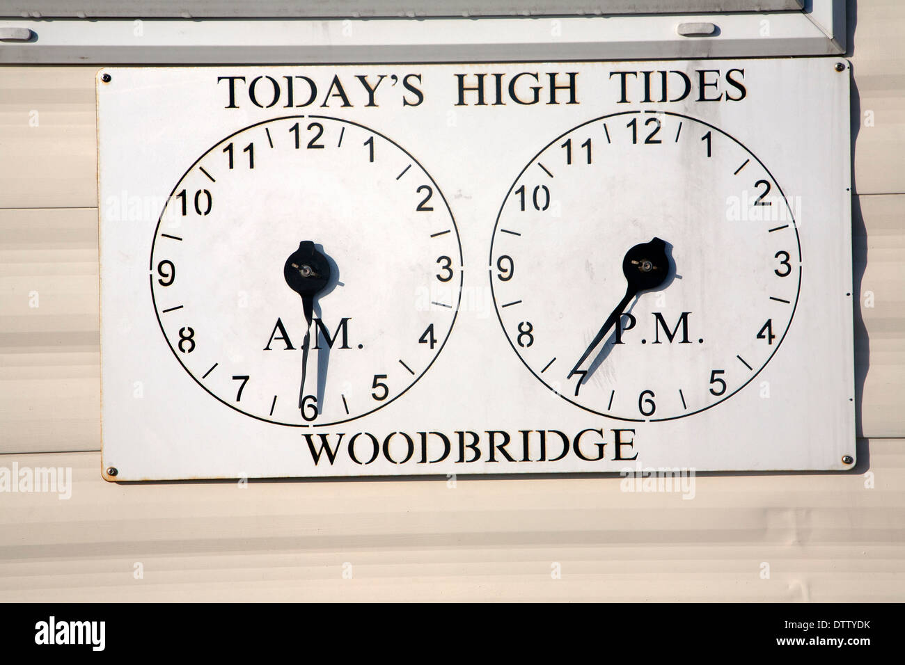 Two clocks showing times of high tides at Woodbridge, Suffolk, England - Stock Image