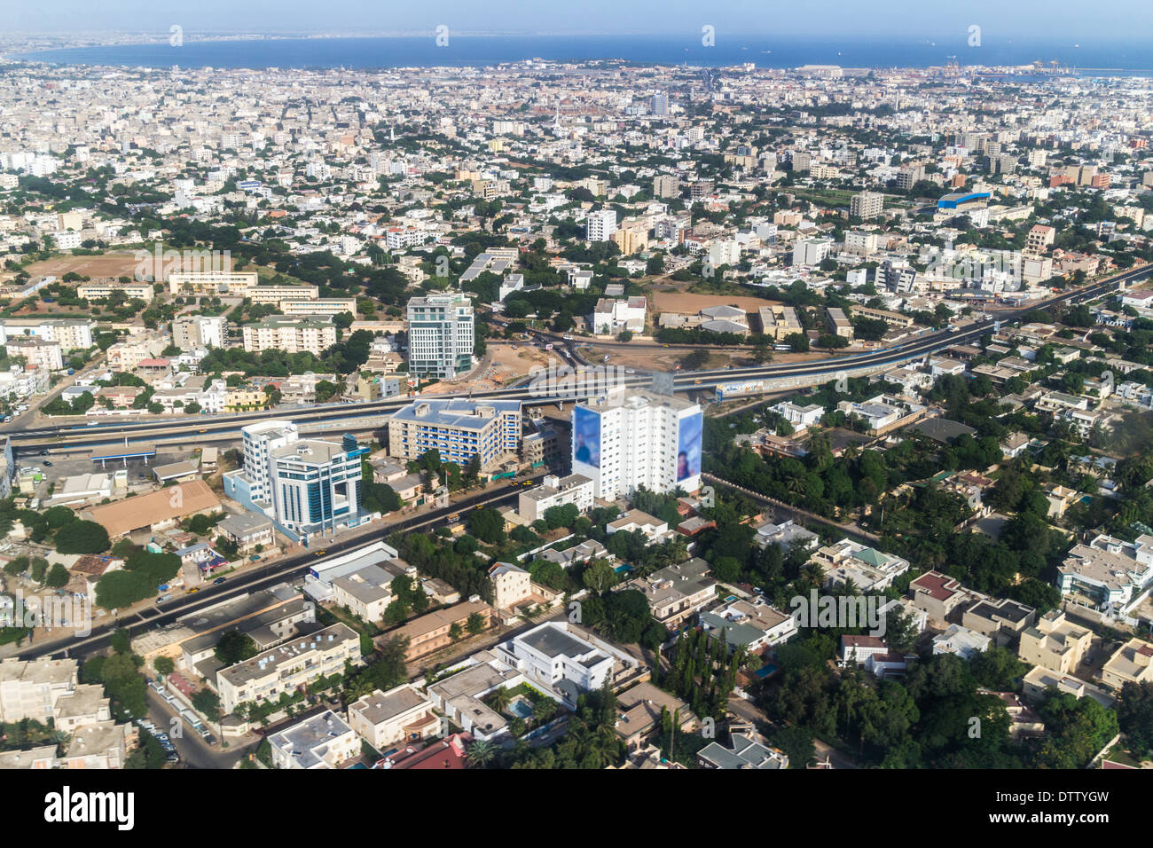 Aerial view of the city of Dakar, Senegal, showing the densely packed buildings and a highway - Stock Image
