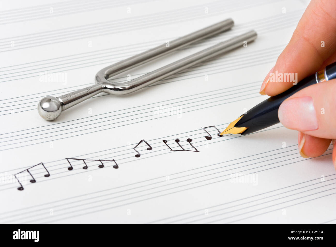 Hand with pen and music sheet - Stock Image