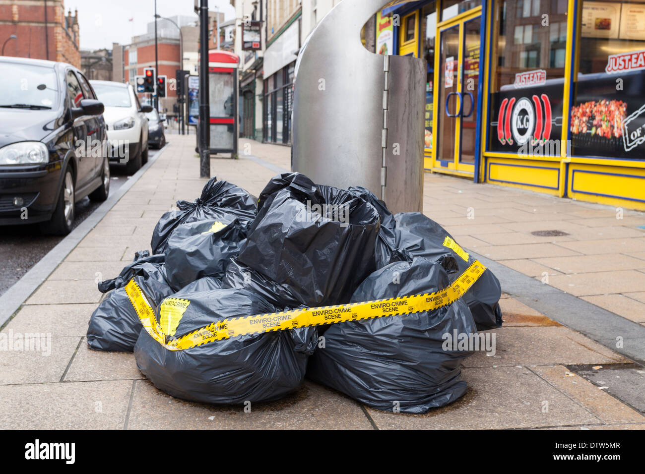 Illegal dumping of bags of waste. Enviro crime scene tape attached. Fly tipping rubbish on a street in Sheffield, England, UK - Stock Image