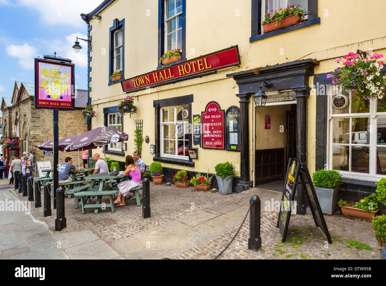 People sitting outside the Town Hall Hotel pub in the historic Market Place, Richmond, North Yorkshire, England, Stock Photo