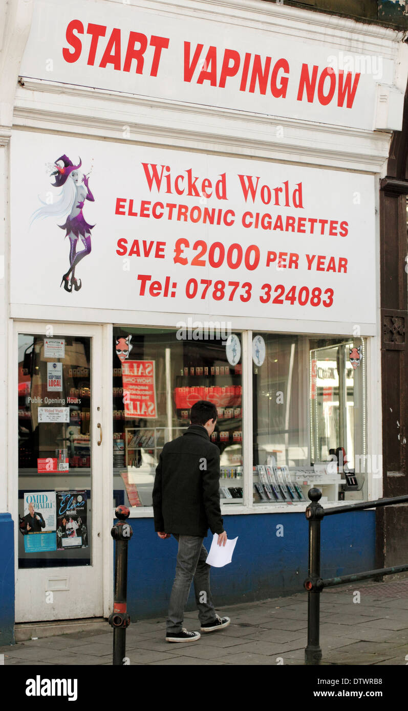 Man walking past  a shop selling electronic cigarettes in Derbyshire, England, UK - Stock Image