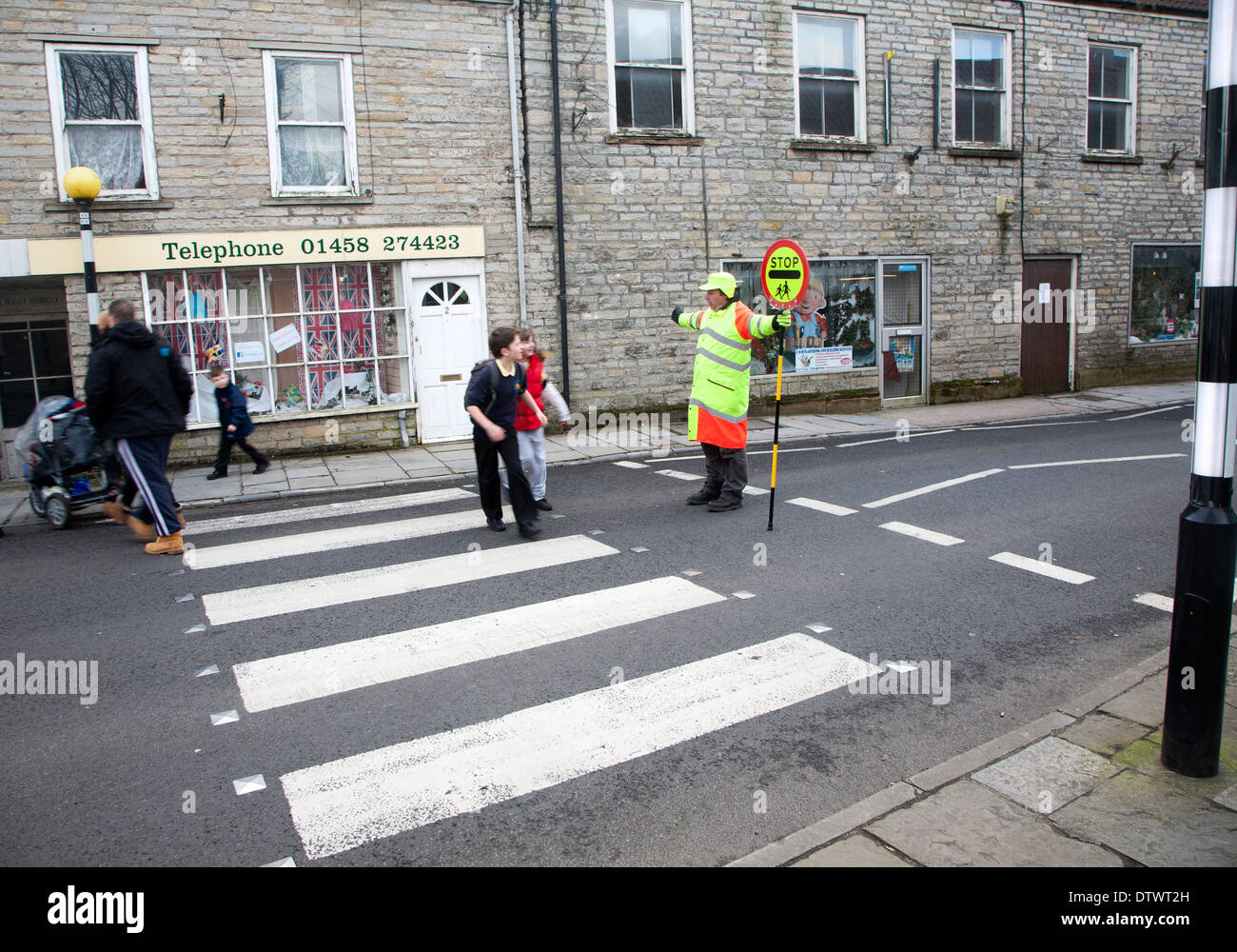 Lollipop man stopping traffic to allow people to cross the road safely, Somerton, Somerset, England - Stock Image