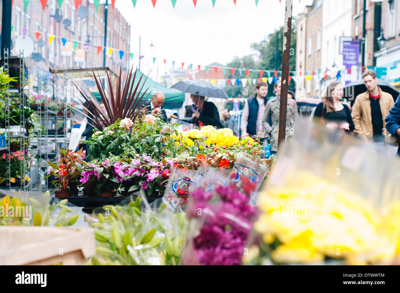 People out at Columbia Road market in east london with flowers in the foreground - Stock Image