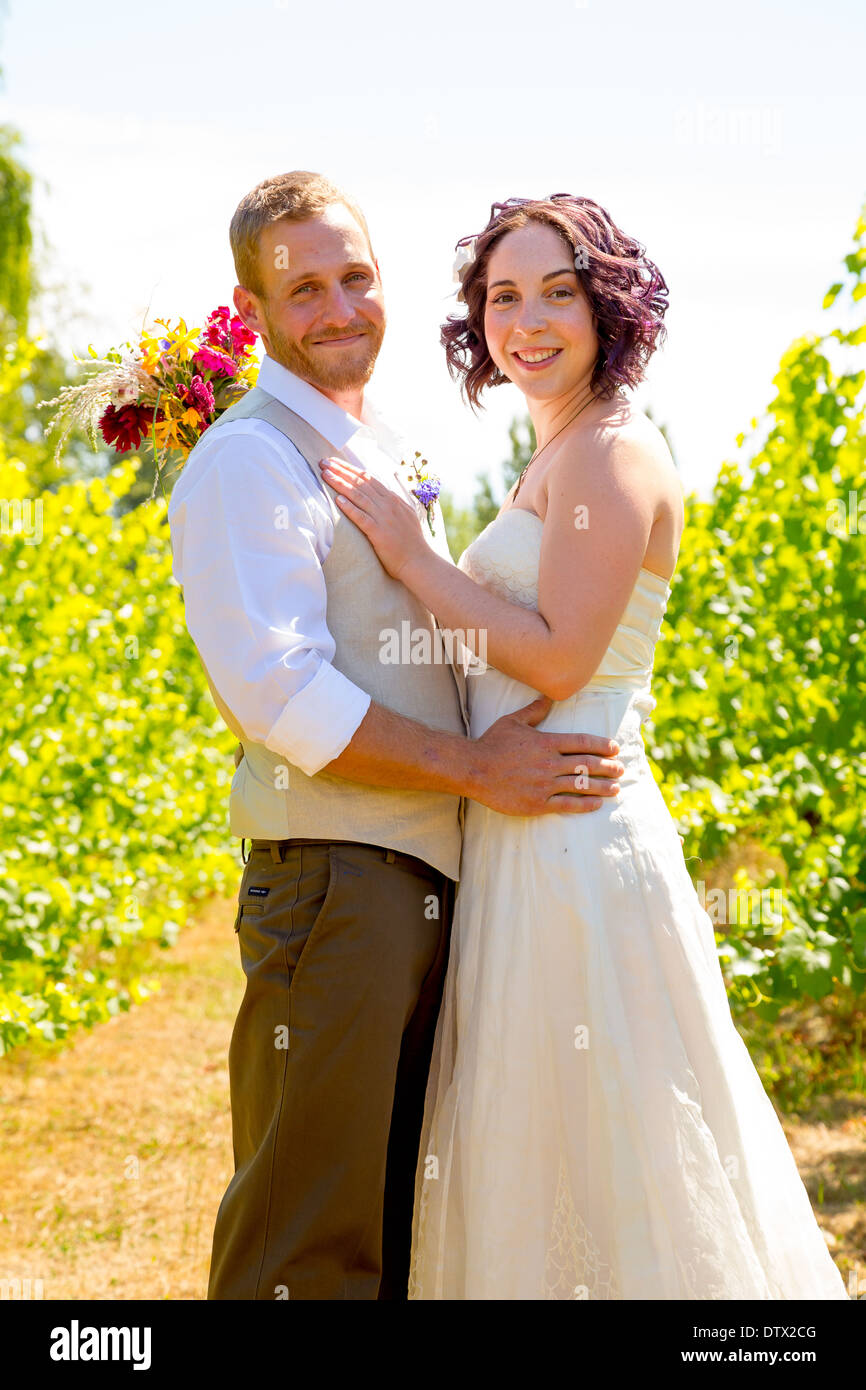 Bride and groom together for a portrait in a vineyard in Oregon on their wedding day. - Stock Image