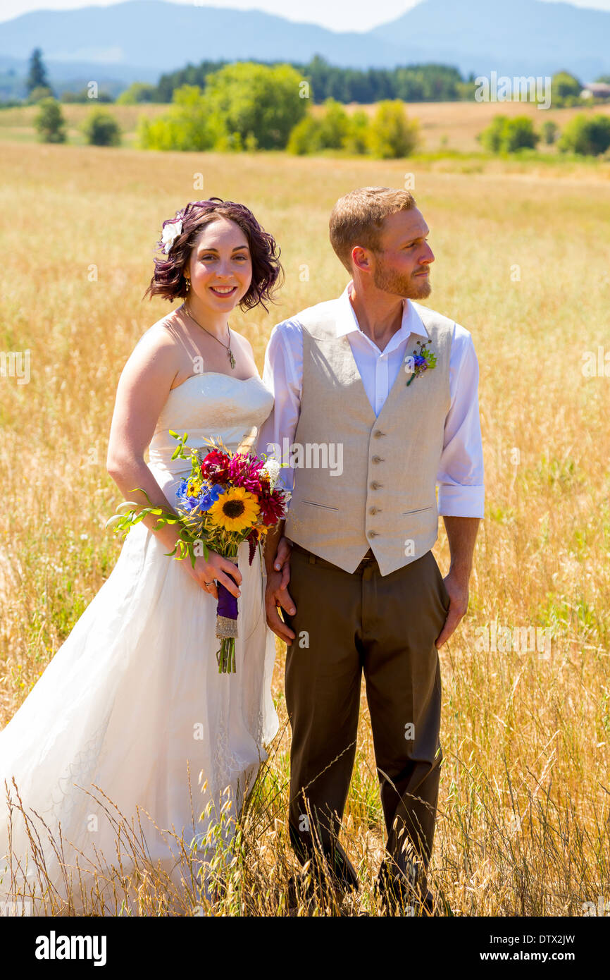 Bride and groom together on their wedding day through a field in Oregon. - Stock Image