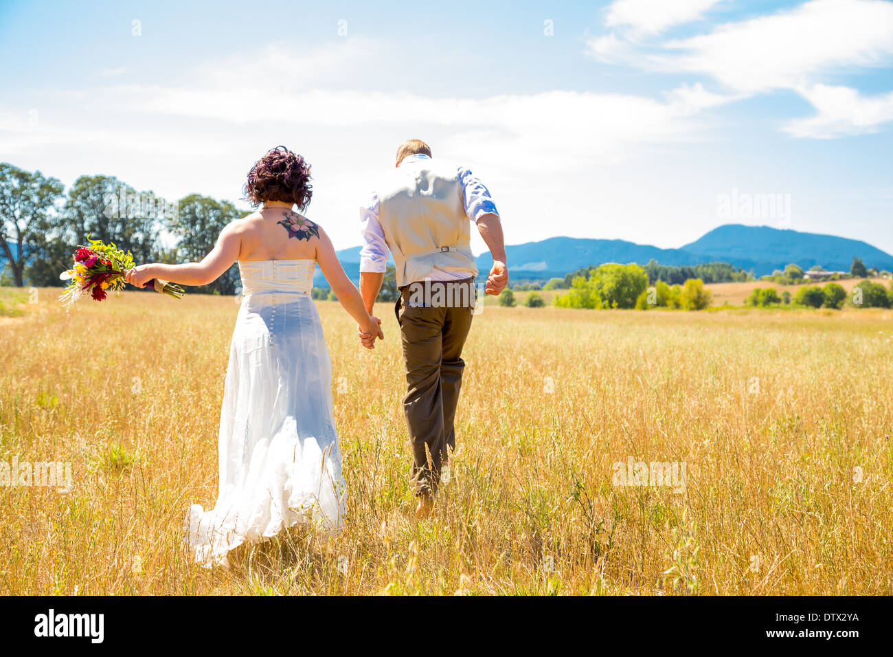 Bride and groom walking together on their wedding day through a field in Oregon. - Stock Image
