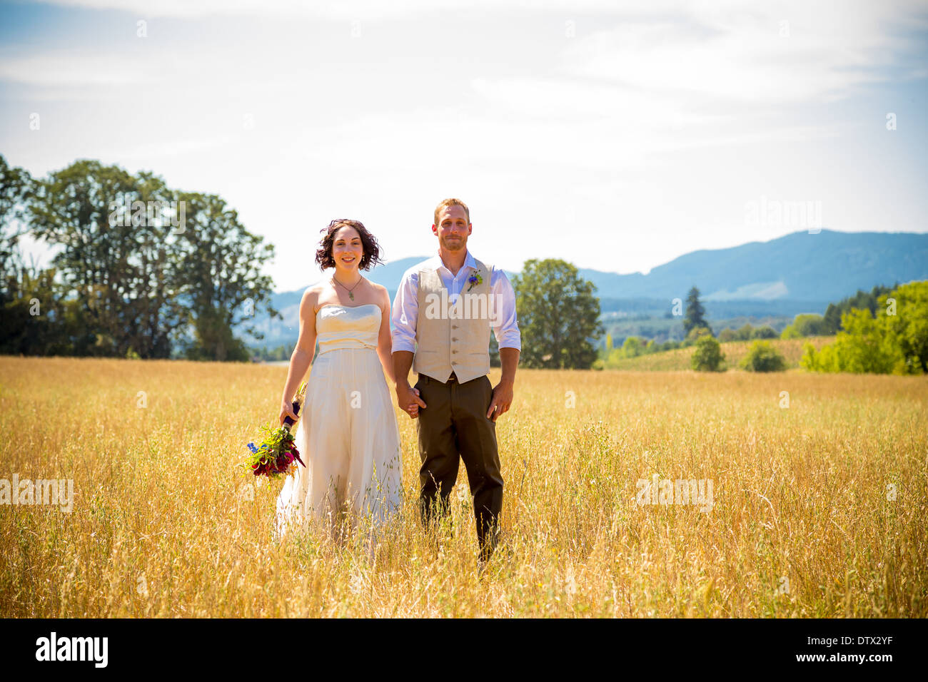 Bride and groom standing together in a field on their wedding day. - Stock Image