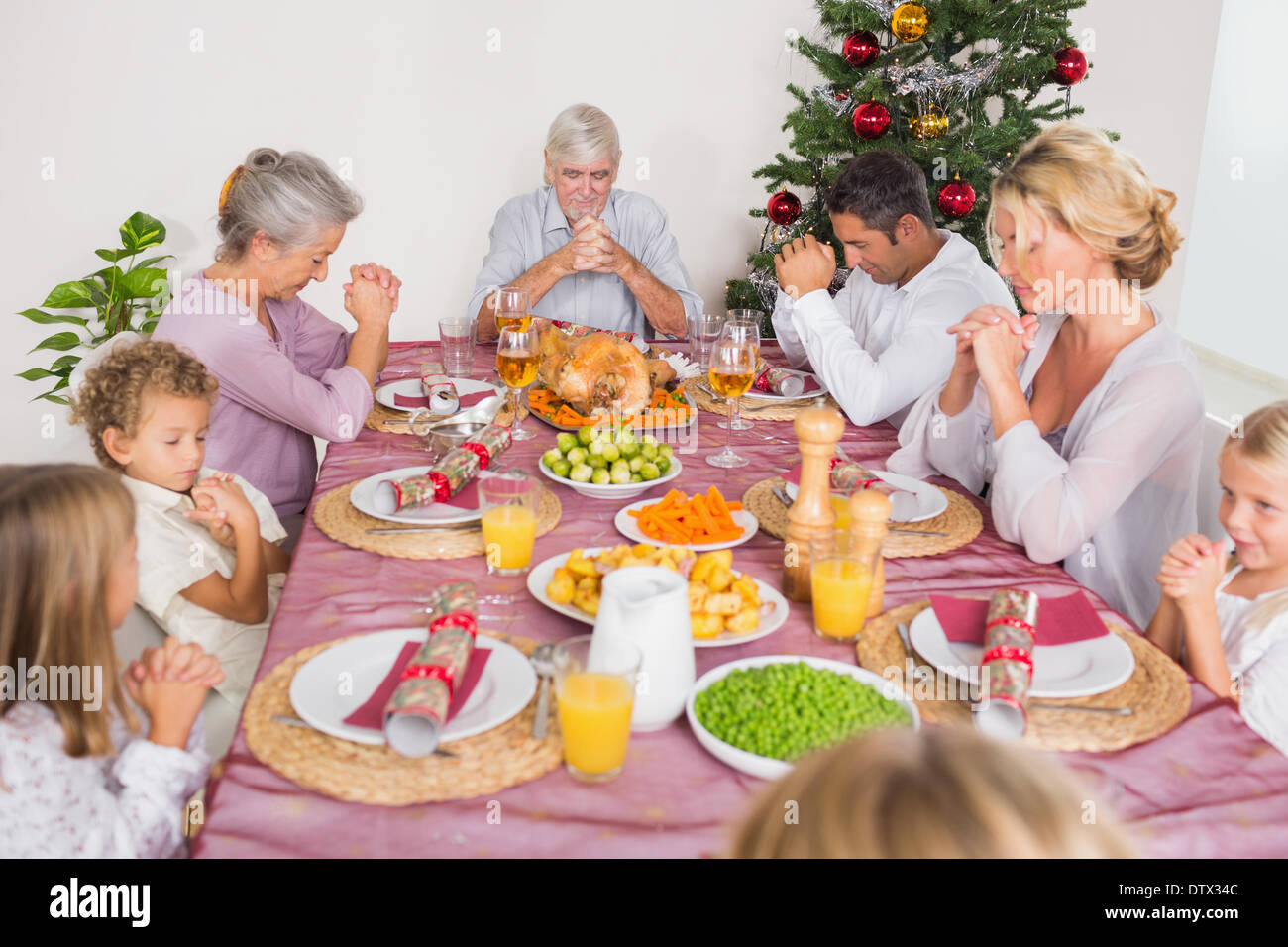 Family saying grace before christmas dinner - Stock Image