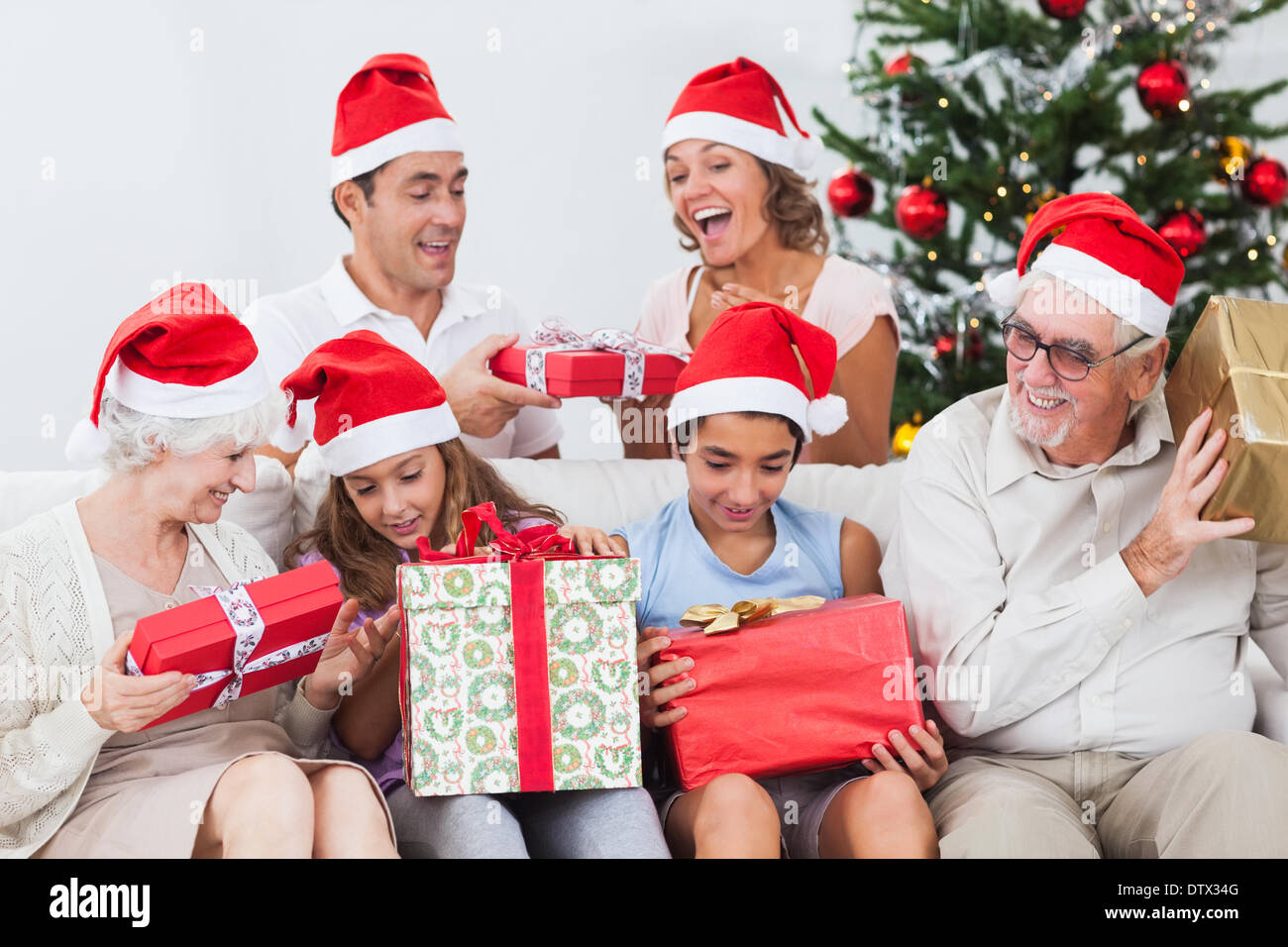 Excited family exchanging gifts at christmas - Stock Image