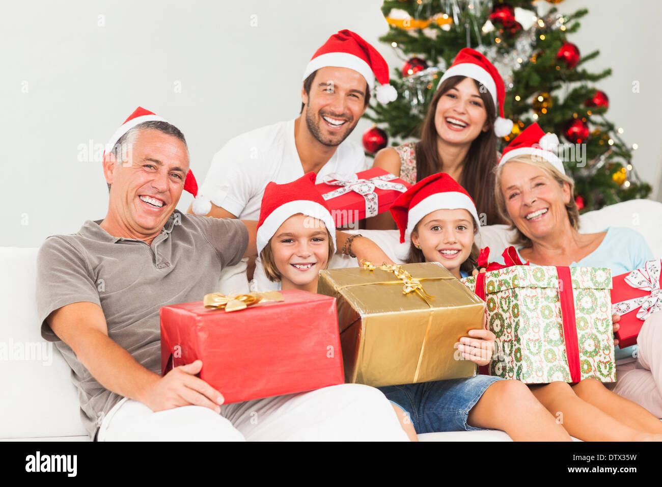 Happy family at christmas holding gifts - Stock Image