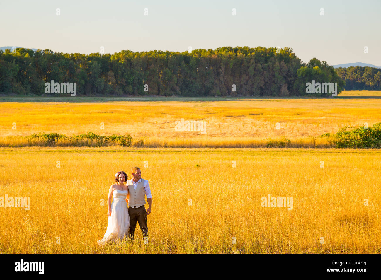 Wedding couple shares a romantic moment in a field or meadow at sunset on their wedding day. Stock Photo