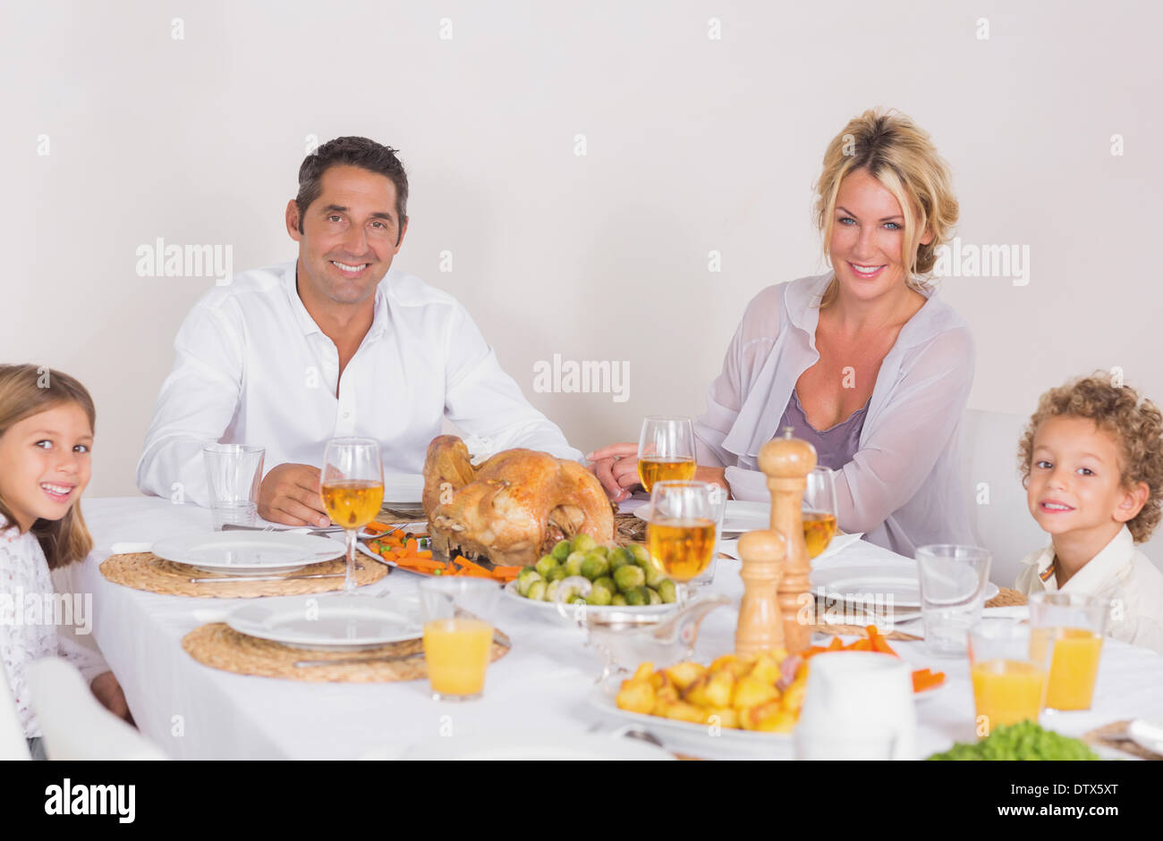 Family sitting on table to eat - Stock Image