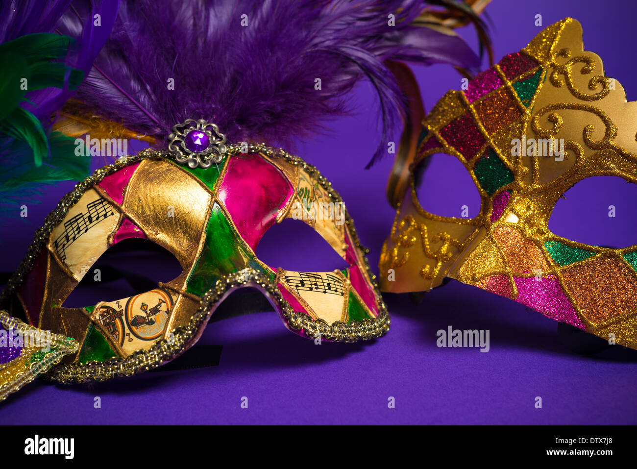 Festive Grouping of mardi gras, venetian or carnivale mask on a purple background - Stock Image