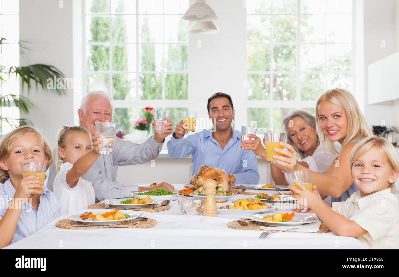 Happy family toasting at thanksgiving dinner - Stock Image