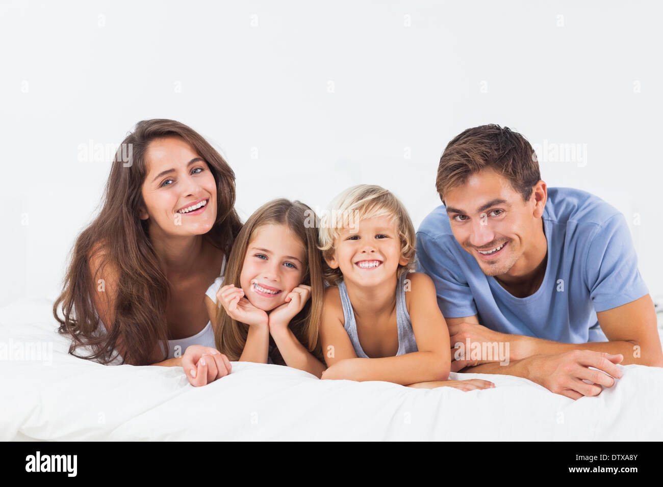 Happy family lying on a bed Stock Photo