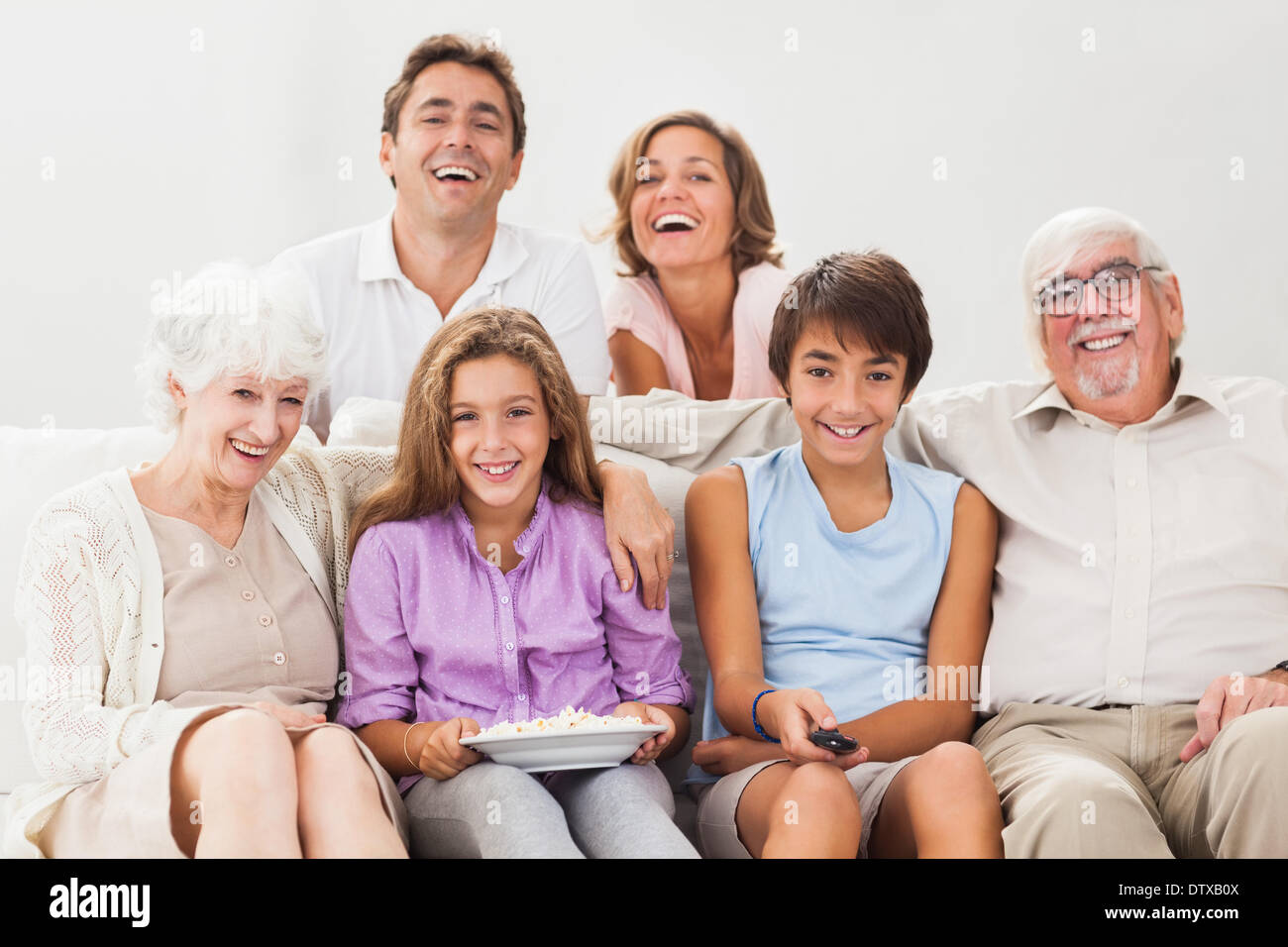 Multigeneration family on couch watching tv Stock Photo