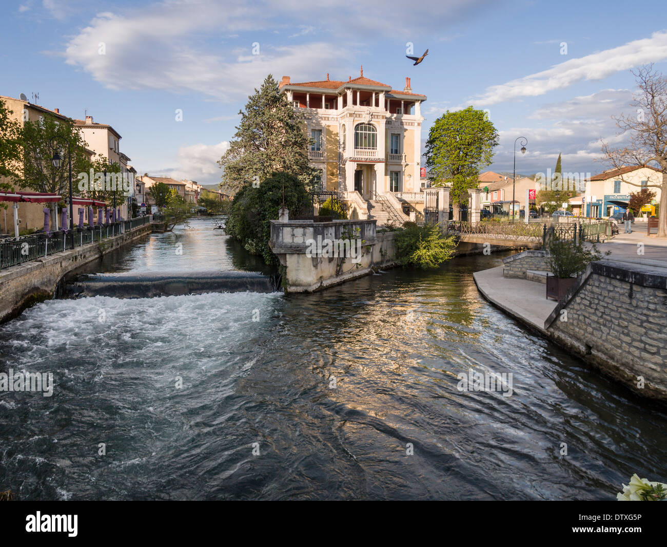 At the confluence a duck takes off. At the joining of two of the many streams in this small Provençal town stands a mansion - Stock Image