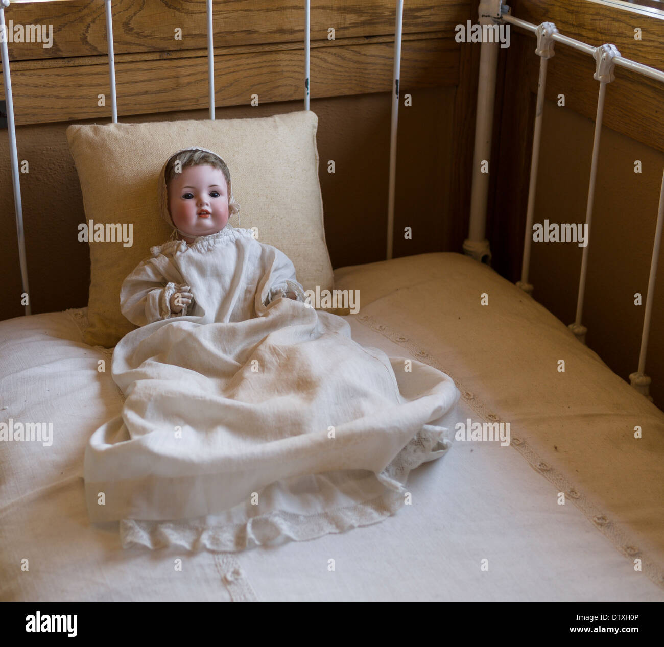 Old porcelain doll propped up in an antique metal crib . An early twentieth century doll decorates the Meyer May House - Stock Image