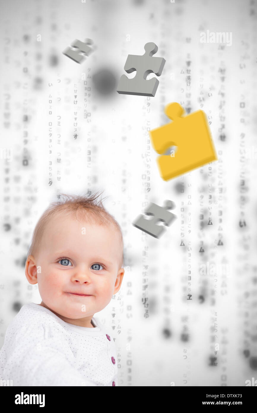Jigsaw pieces floating around a baby - Stock Image