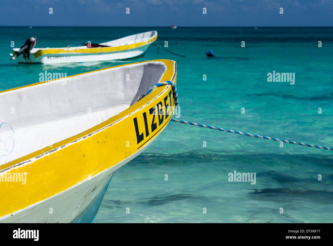 Tour Boat Lizbeth beached. A traditional snorkeling and Tulum ruins tour boat anchored in blue green waters off the town beach - Stock Image