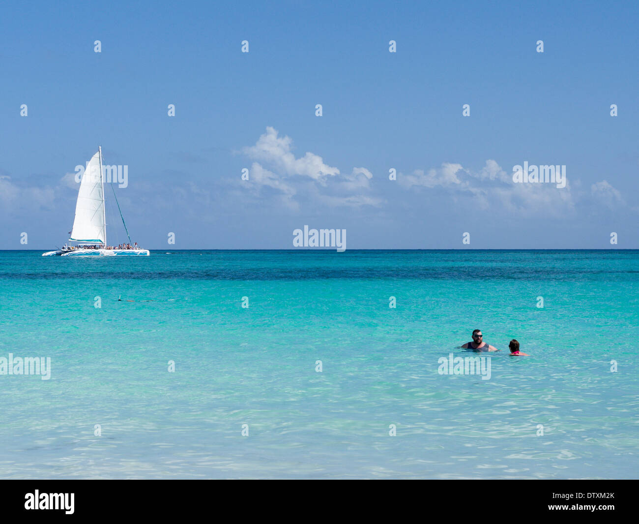 Swimming, snorkeling, sailing at Tulum Beach. The calm blue waters of Tulum beach with swimmers, snorkeler and a snorkel boat - Stock Image