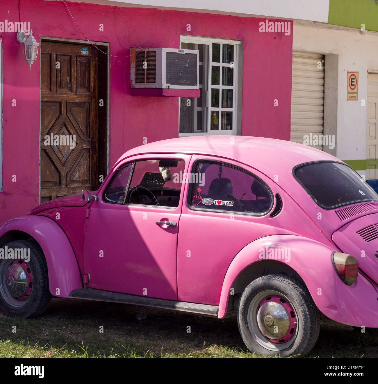 Pink VW and Matching House. A bright pink Volkswagen beetle parked in front of a pink house. Tulum, Quintana Roo, Mexico - Stock Image