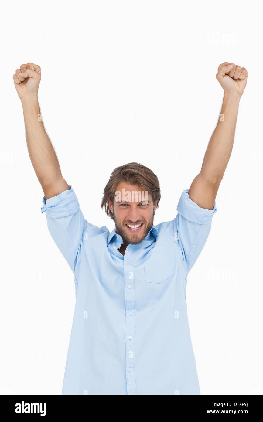 Happy man celebrating success with arms up - Stock Image