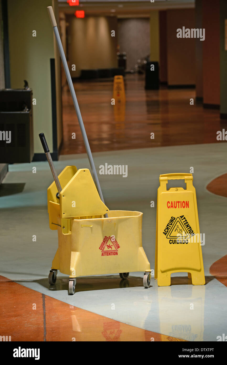 Mop and Bucket with caution sign on wet floor - Stock Image