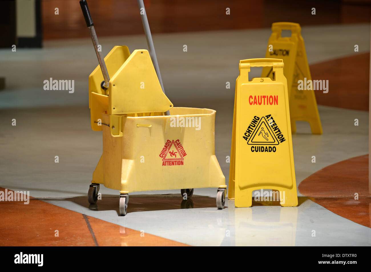 Janitorial mop and caution sign on hallway - Stock Image