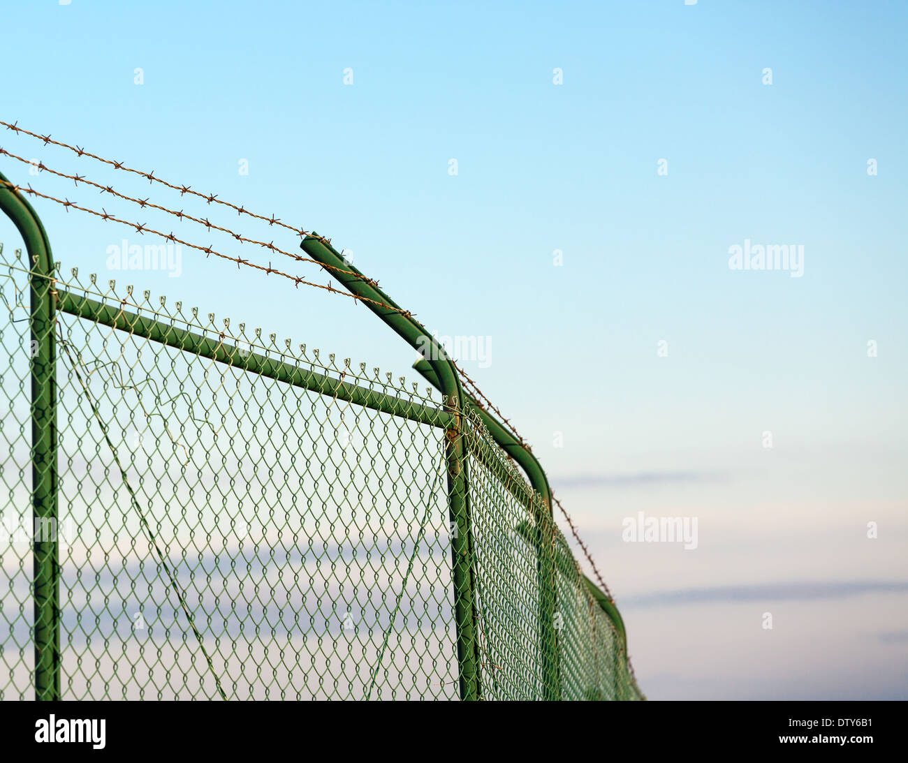 Mesh fence with barbed wire on a background of blue sky - Stock Image